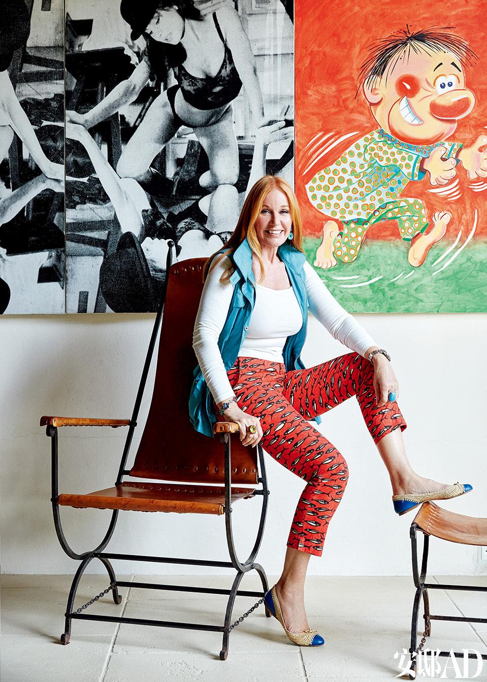 """坐在扶手上的Suzanne,扶手椅和脚凳均来自André Arbus。后侧的油画来自Julia Wachtel。主人: Suzanne Syz(苏珊·塞兹),瑞士珠宝设计师,20世纪80年代活跃于纽约,与安迪·沃霍尔、巴斯奎特(Jean Michel Basquiat)、施纳贝尔(Julian Schnabel)、杰夫·昆斯(Jeff Koons)等知名艺术家过从甚密。近年搬到日内瓦,她的作品经常出现在各大秀展:棕榈滩珠宝与古董展(Palm Beach Jewelery Show),""""军械库展会""""(Armory Show),日内瓦艺术展(Art Genève)和伦敦大师展(Masterpiece London);对艺术收藏保持热情的她,也常在PAD、弗里兹艺术博览会(Frieze)、巴塞尔艺术展(Art Basel)、TEFAF等各大艺廊和艺术展上寻找新藏品。"""