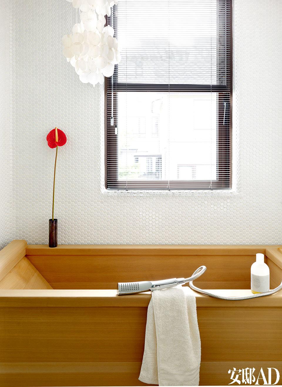一个砌满白色马赛克的浴厕,浴缸为手工特别定制,使用特殊的阿拉斯加扁柏木材质。