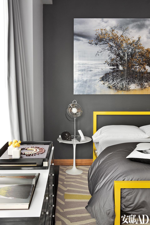 """""""我们想要一间黄色调的客房,这幅摄影作品终于成为串联整个空间的线索。""""客房,床头挂着一幅摄影师Isack Kousnsky的照片,床架来自Room & Board,地毯来自West Elm ,床头夜桌来自Knoll,台灯为Artemide。"""