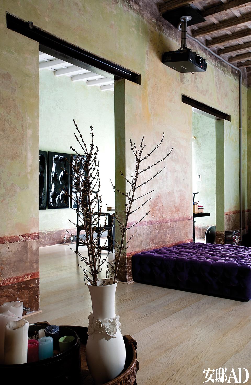 从起居室能看到书房一景。La Michetta紫色绒面沙发由Gaetano Pesce为Meritalia设计。复古木桌上摆放着蜡烛和白色陶花瓶,里面的植物营造出了中国蜡梅的效果。
