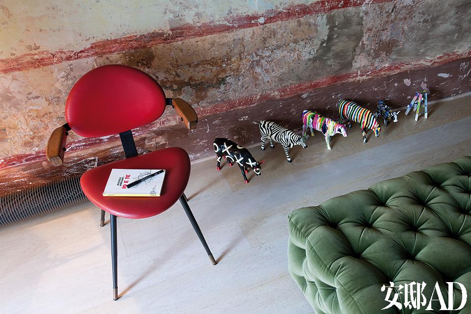 起居室细节:Mollino不锈钢座椅有着红色椅身。Meritalia沙发,Cow Parade的陶牛。