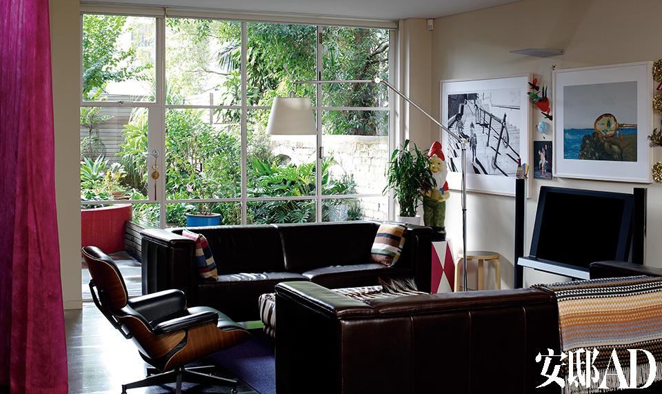 """房屋改造的重点之一,就是尽可能多地打开客厅与花园之间的墙体面积,将阳光与绿色生动地引入室内。钢制细框玻璃窗将葳蕤的花园最大限度地引进客厅中,两只Brescia Furniture的双人皮沙发上搭配了Missoni的彩色靠垫,旁边立着一座Artemide品牌的Tolomeo地灯以及Herman Miller出品的Eames躺椅,上方的壁灯来自Targetti Squadra。墙上的三幅艺术品从左起分别是Matt Coyle的""""Worry Dolls Setting Out""""、Shonah Trescott的""""Susanna and the Elders No.12"""",以及Elaine Campaner的""""Ballina""""。"""