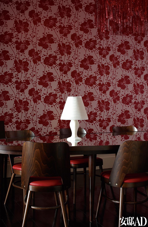 镜面餐桌倒映着壁纸上的图案,令餐厅更加梦幻而温暖。主客厅丰满的红色墙面由Florence Broadhurst的斑点花纹墙纸打造而成,Signature Prints出品,Thonet品牌的Otto餐椅带着巧克力色调。餐桌也是定制品,桌上的白色蜂窝状台灯来自Kyouei Design。