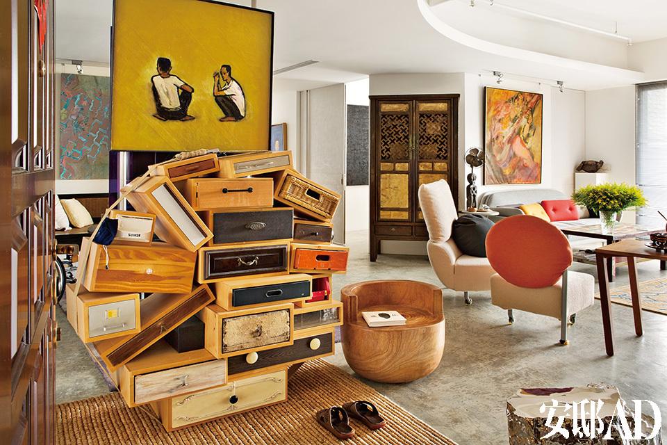 开放式起居室分隔出客厅及用餐空间,有明末清初的软木柜子,表面没有繁复雕刻,2.5米高的南方家具设计目前仍为仅见。右边的铜制电风扇是美国上世纪50年代的古董;墙上挂着印度艺术家Krishen Khanna的油画作品《Portrait of Ali Akbar Khan》。如纽约Loft风格的开放空间中,荷兰前卫幽默抽屉柜,与明末清初的柜子同处一室,就是一点也不冲突。