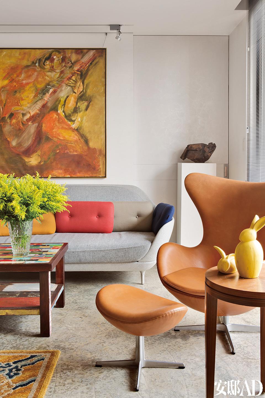 姚谦特别欣赏设计师Jaime Hayón的作品,尤其是这张由Fritz Hansen出品的灰色FAVN沙发,一旁是著名的Egg皮革单椅;后面木头雕塑为朱铭的《母鸡》;彩色茶几由一位法国艺术家用巴厘岛的废弃船只制作而成。一张北欧蛋椅,是姚谦经常发呆的地方,有时看看画作,有时望着落地窗外,看风云变幻。