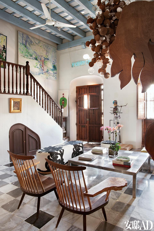 楼梯处挂有Sissel Kardel的画作,其下方是Jorge Pardo的画作。金色裱框内是一幅18世纪的油画,作者不详。这里的家具由日籍美国木匠大师George Nakashima手制而成,精致中还带有丝丝加勒比风情。