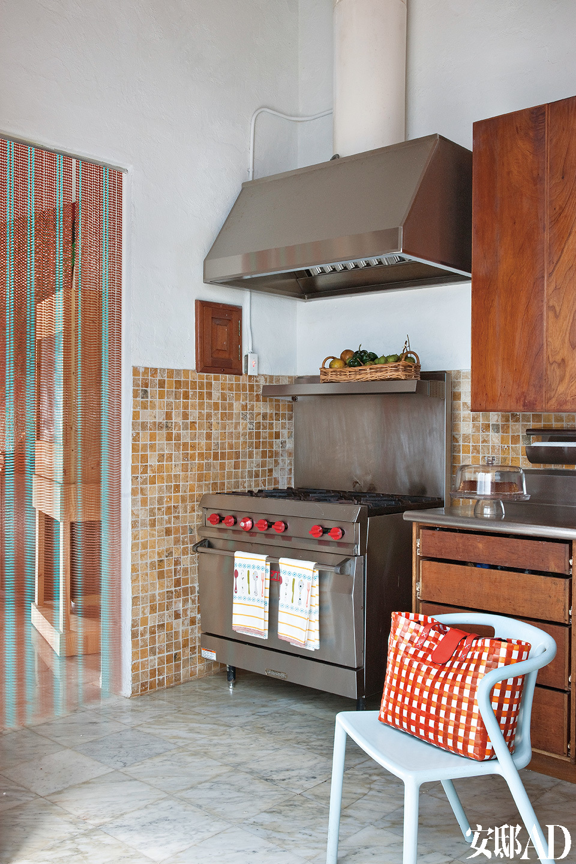 厨房内摆放着Jasper Morrison设计的椅子,竖条门帘出自Chris Ofili之手。
