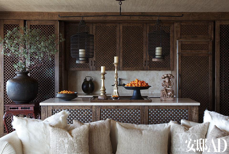花格木门打造的厨房别具异域风情,中式灯笼烛台更丰富了装饰层次。 黑色铁质灯笼来自中国,前景处乳白色、象牙色等中性色调的靠垫很好地缓和了后景里深色装饰的沉重感。印尼大托盘来自ABC Carpet & Home。
