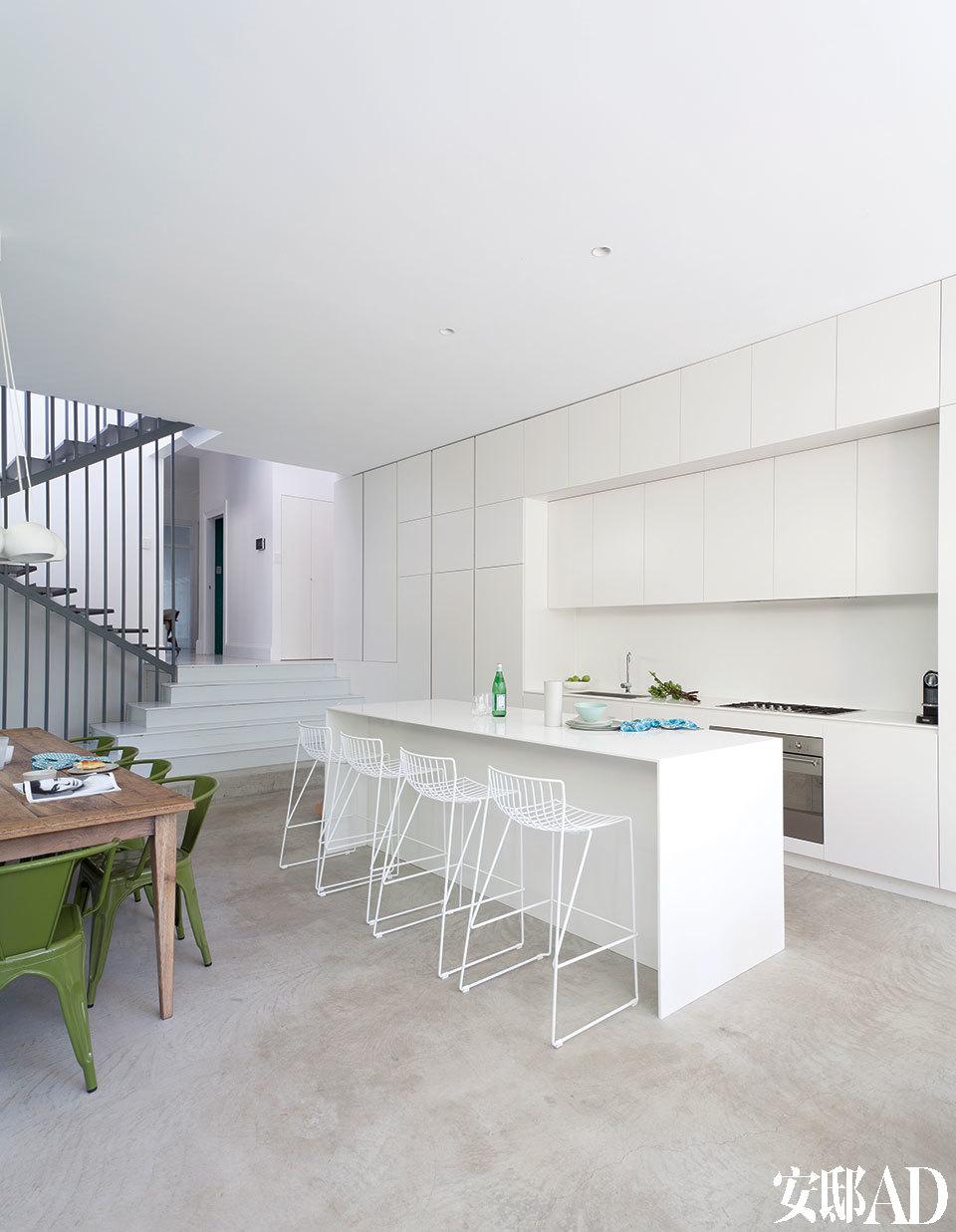 厨房的线条十分简洁明了,橱柜空间充足,一切厨房用品都有其收纳之处。厨房储物柜是在Jayden Innovations定制的,厨房操作台和中央岛台也来自Jayden Innovations,为亚光白色可丽耐材质。餐凳来自Spence & Lyda。