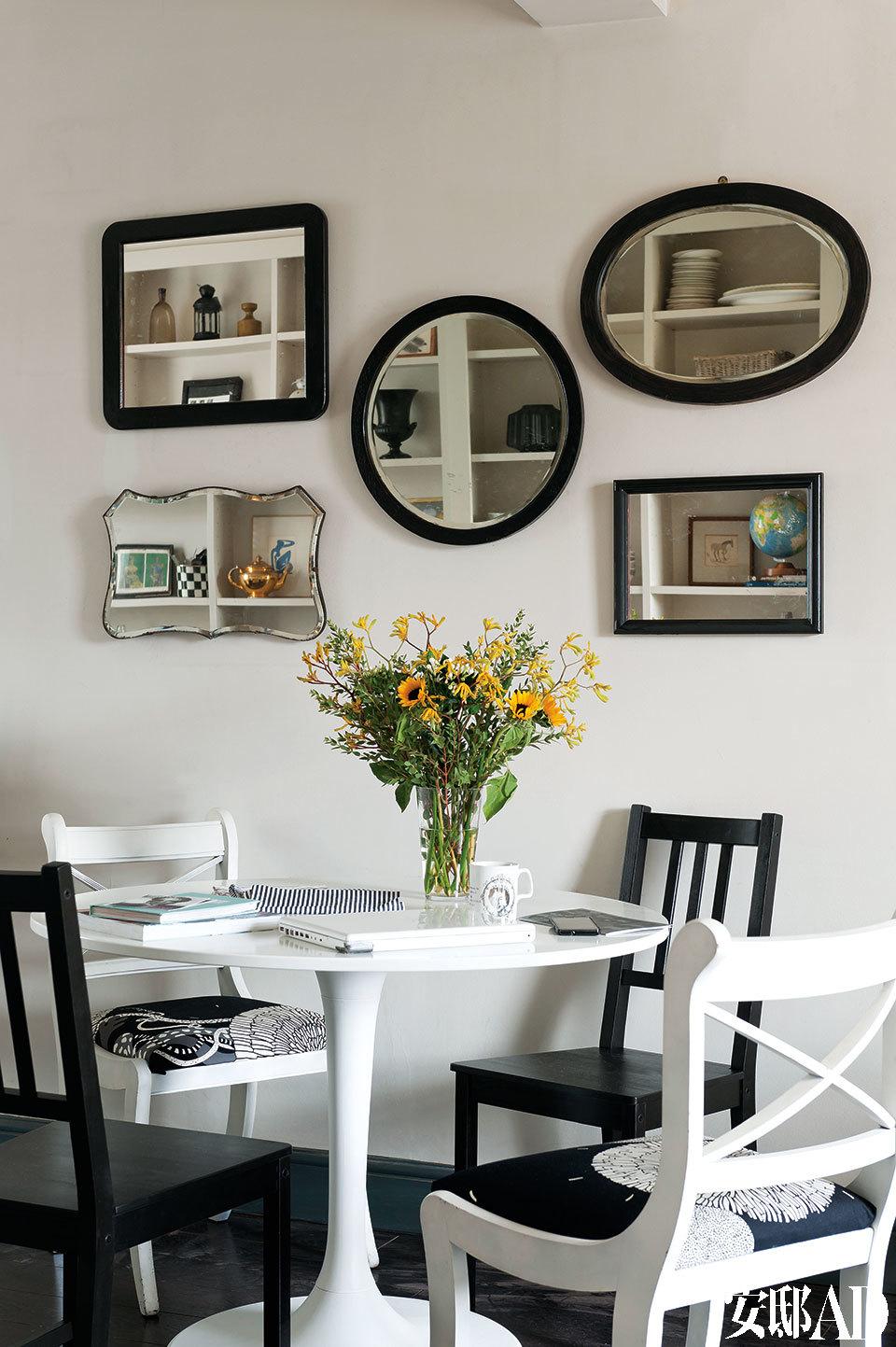形状不同的复古镜,装饰着餐桌旁的墙面,还倒映出对面储物架上的各式收藏。餐厅就设在客厅的另一头,使用了来自宜家家居的餐桌和黑色厨房座椅,白色座椅则来自Sussex Country Brocante。墙上的装饰镜来自Peanut Vendor。