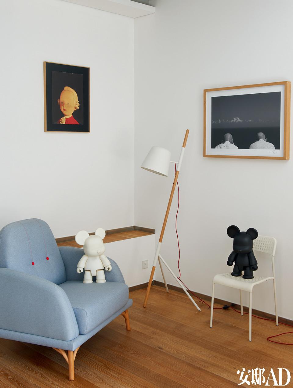 """楼上卧室区,单人扶手沙发来自本土设计师品牌""""吱音"""", 落地灯是北欧设计师的作品,购自德国。左侧的画作是刘野的《小小莫扎特》,右侧的摄影作品来自高鸣。"""