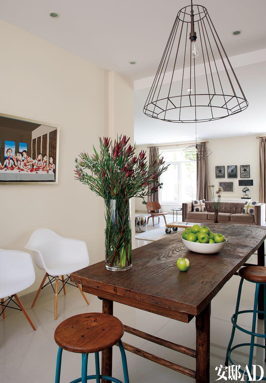 书房与客厅相接,一张明代的书案来自上海Hu&Hu古董店,两张圆形吧凳来自北京798艺术区的Burma- Cottage东舍,靠墙的两张扶手椅是Eames设计的复刻版,铁艺吊灯由Hong设计出品。