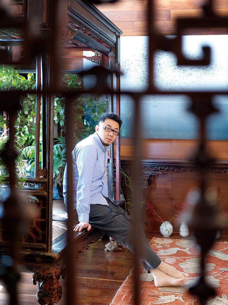 """透过屏风的窗格,可以看到迟鹏坐在客厅的福建雕花架子床上,他说,""""福建老床大多雕龙戏凤,这张床只用窗格子,显得很素,而且工艺精细,当年的主人品位一定很高。""""旁边龟背竹和鹅掌柴正掩映着老床榻,地上绘着白色仙鹤与莲叶的橘色老地毯则让客厅多了明媚与生机。"""