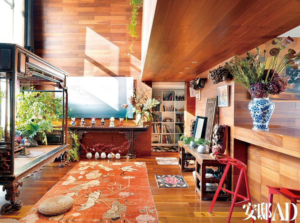 在客厅中,地板和大部分墙壁都被贴上深色原木板,桌椅案几和收藏的老物件几乎都是木头材质,而地上大大小小的老地毯也带有怀旧和温暖特质。拍摄当天,阳光 非常好,从老床榻背后的落地窗外斜照进来,与室内景致相映成趣。自言因太过敏感而缺乏安全感的主人,在打造这个家时,将对温暖的迷恋作为首要情绪基调。