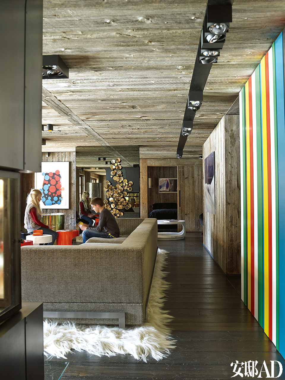 客厅中宽大的沙发是设计师Thierry Lemaire为这个空间特别定制的,漆面茶几也是Thierry的设计。木墙上油画的作者是José Pedro Croft,一旁在形状上与其相呼应的镜面艺术品由Curtis Gere创作,天花板照明装置使用了Modular。