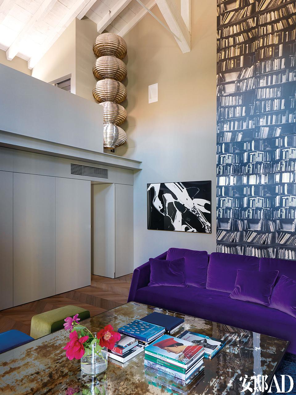 """彩色沙发及银色吊灯,打破了两层楼高黑白书架壁纸所带来的""""压抑""""。客厅中的宝石色天鹅绒沙发由Martina Gaslini为这个家量身打造,高处的银色雕塑一下子提亮了顶楼。"""