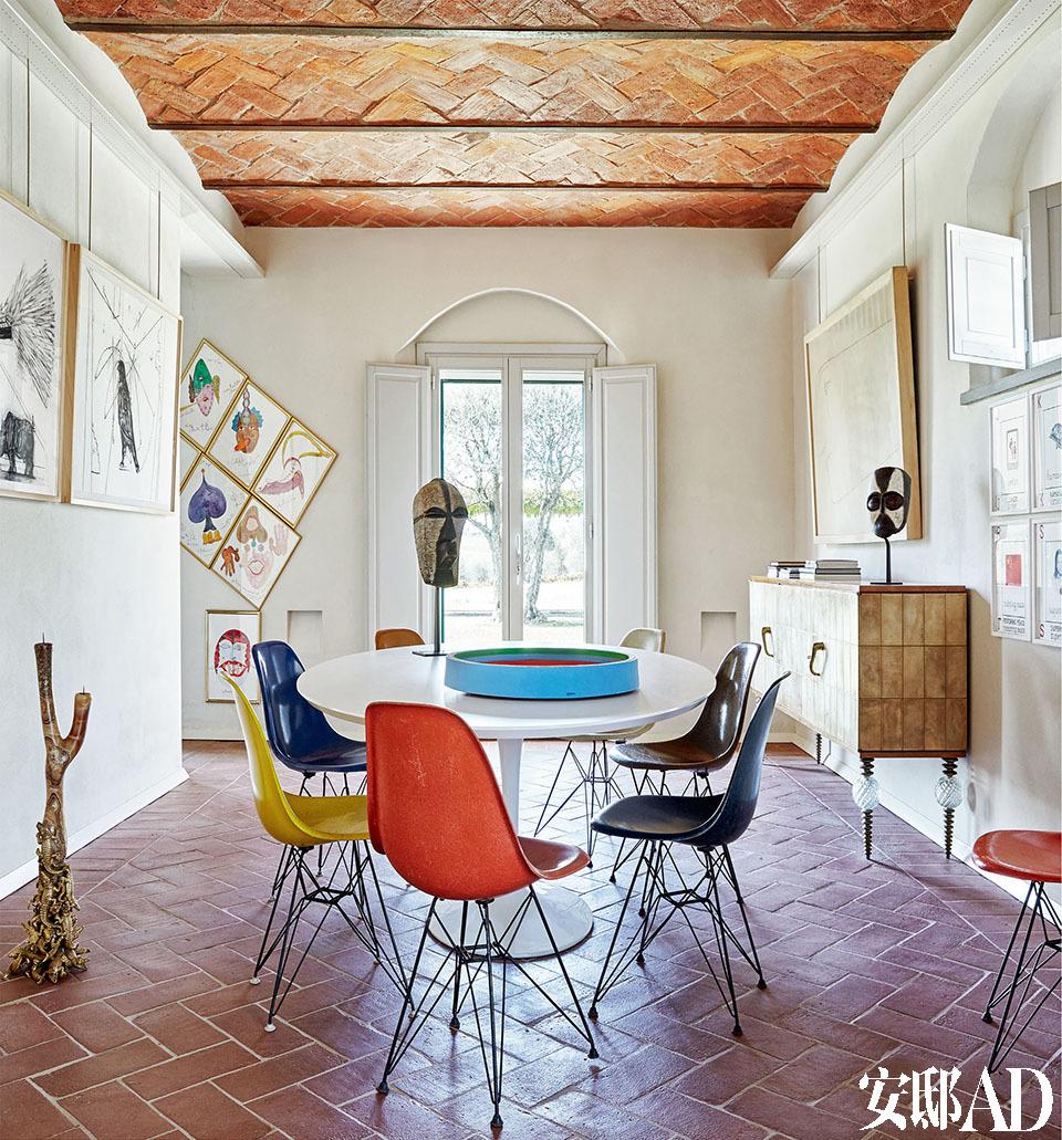 """""""自由,是购买艺术品时最重要的价值。"""" 餐厅里,左边墙上挂的是William Kentridge作于2005年的Preparing the Flute ,地上的烛台是Campana兄弟设计的""""Lacrime di coccodrillo"""",窗边墙上的是Luigi Ontani的画作Musical Masks ,餐桌和餐具都出自Eero Saarinen之手,右边墙上挂的是Giuseppe Stampone于2009年的画作ABC America ,边柜是意大利设计师Paolo Buffa在20世纪40年代的作品。"""
