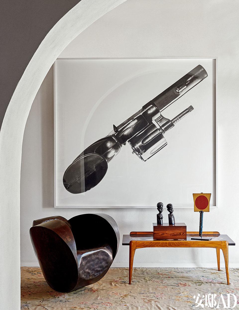 "Robert Longo于2005年的画作Untitled (357 Reload)。Pietro Chiesa为Fontana Arte设计的20世纪40年代茶几。茶几上摆着17世纪日本军队的传统方形铁扇,Ron Arad 1989年设计的扶手椅""Rolling Volume""。"