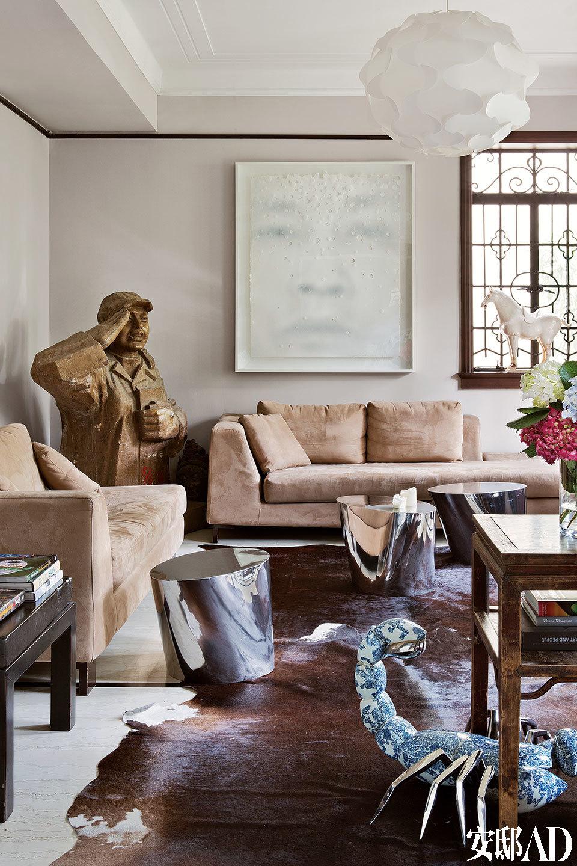 """""""因为别的项目需要资金,我跟Beatrice提议卖掉一些艺术品,她却无法赞成。这意味着你知道艺术品背后的故事越多,就越难与其割舍!""""主人收藏着的中国艺术品大多带有强烈的文化、时代特征。在沙发之间的墙角,竟然挤进了一尊对于室内空间而言相当大型的王广义雕塑作品,这是一个充满理想色彩而又失却性别特征的女性形象,让我们立刻想起那个""""不爱红装""""的年代。金属圆凳来自明合文吉。顶部的白色吊灯是宜家的设计。"""