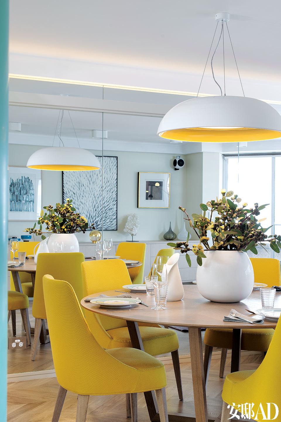 餐桌旁沙发背后是一整面镜面墙,对面的电视柜及窗外的海景全映在里面。餐厅使用了Hub Furniture圆形定制橡木桌,黄色的Maxalto座椅来自Antonio Citterio品牌,粗木腿设计显示出明快风格。镜子中倒映出对面墙角白色的流线型书柜,柜子上方悬挂着主人收藏的艺术作品。