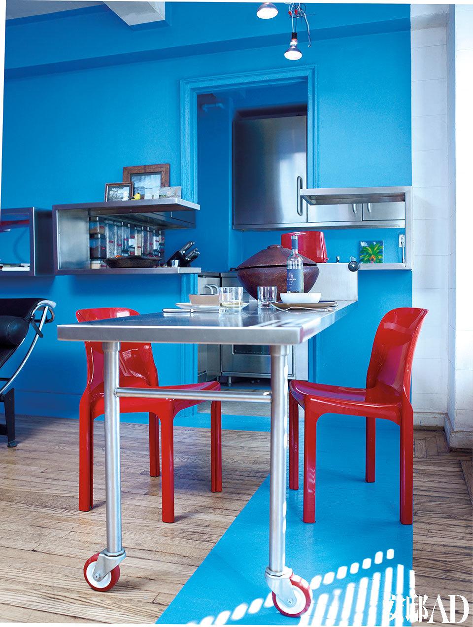 带有滚轮的餐桌能随意移动,这种弹性设计对小空间而言非常重要。地板的蓝色基底有参照位置的作用。Selene红色座椅由意大利设计师Vico Magistretti设计。厨房架子上的瓶瓶罐罐都被主人打上了标签。