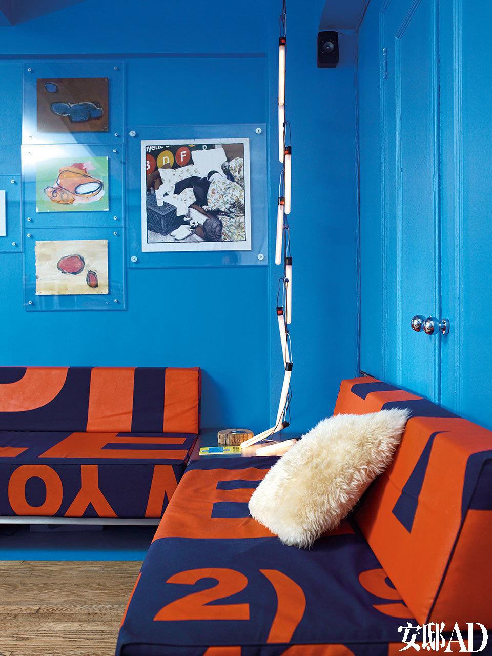 打开沙发背后的柜门,一张宽敞的沙发床藏在里面,而床尾就是露在外面的沙发。沙发为定制产品,由Giuseppe Lignano设计,其面料是二手的帆布(含有遮光成分),上面的图文则是Giuseppe在纽约的地址和电话号码。两美元一个的灯管挨个挂起来,成了颇具个性的照明装饰;墙上竖挂的三幅画作来自John Hartmann,右边的画作则来自纽约艺术家Emmanuel Viotte。