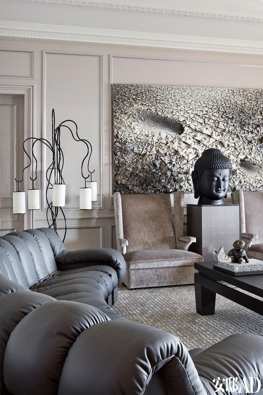 客厅中央,佛像雕塑出自韩国艺术家Noh Sang Kyoon,佛像后面的墙上挂着 Kwang-Young Chun的作品,像藤蔓植物的立式灯是Jean Royère设计的。