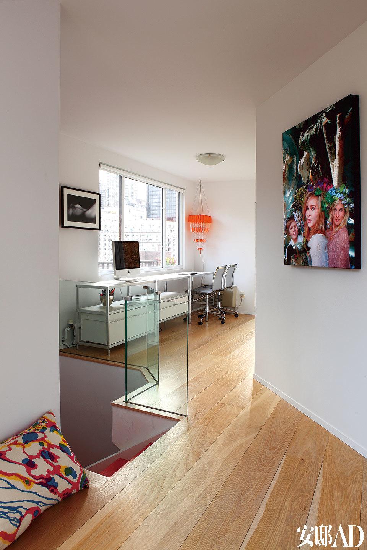 不规则形状的楼梯间,将卧室与工作间分为两个部分,统一的木地板将一种流动感融入整个空间。楼上的一角被利用成了Cecilia开放的工作间,墙上挂着她和孩子们的艺术照片。