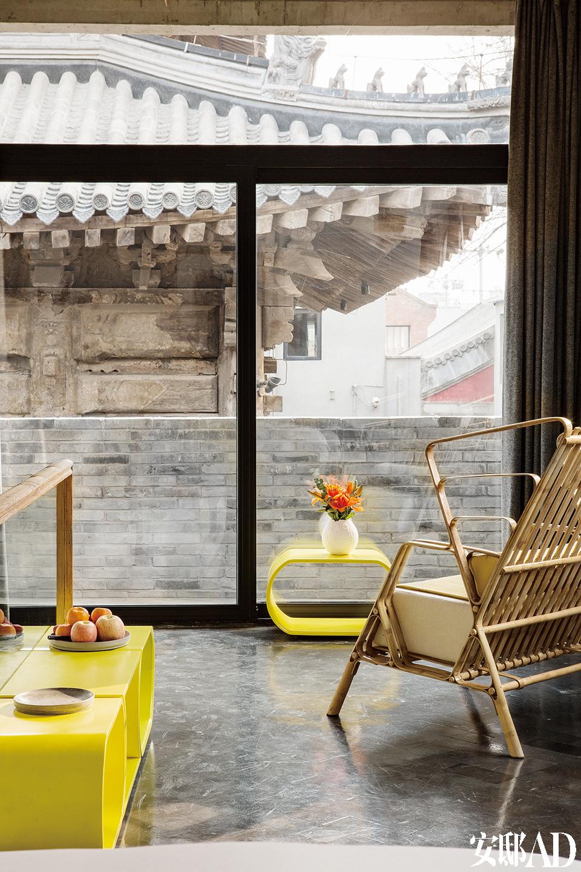 """""""峨眉""""客房里依然配置了Sandeep Sangaru的扶手椅和刘利年的亮黄色子母桌,大落地窗提供了欣赏院落中古建筑的特别视角。精确设计的开窗位置,让古建筑苍劲的瓦楞檐角成为每个房间最美的窗景。"""