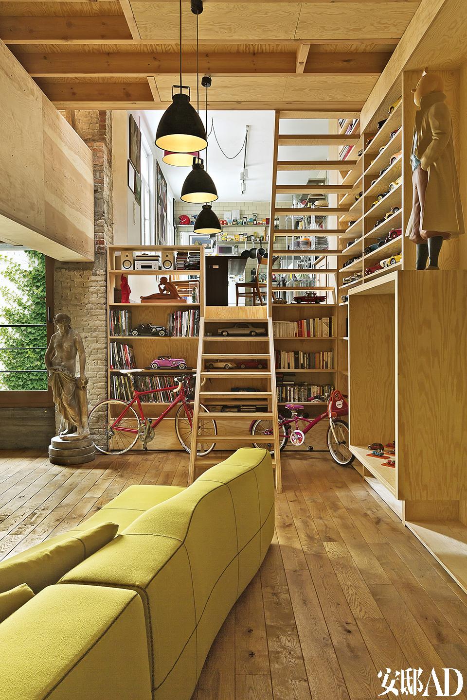 底层的客厅整个被木质材料包裹住,顶棚也采用了木质嵌板,显得非常温馨。名为Augustin的金属吊灯来自Jieldé,带有浓浓的工业感,是法国工业 艺术的形象代表。Bend组合沙发是由设计师Patricia Urquiola为 B&B Italia量身打造的,来自比利时的In Store。