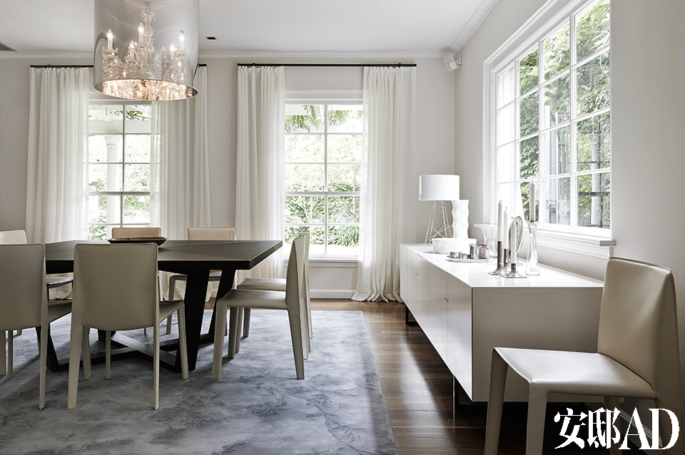 [After] 正式餐厅中薄麻布窗帘搭配着金属质地的挂杆,显得轻盈而通透。来自Maxalto的大号黑色橡木桌Xilos被用作餐桌,围绕它的是10把来自 B&BItalia的Doyl/14餐椅。蛋壳白色的靠窗边柜来自Clementine,桌上的台灯Ray同样由Flos出品。白墙白窗白帘白家具,映着窗外的绿,优雅而宁静。