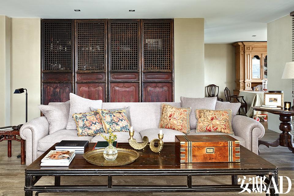 起居室一角,改造后的中式橱柜用来存放书籍和其他家用工具,桌上有摩洛哥金属托盘和19世纪英国木盒,沙发上放着法国刺绣工艺靠枕。
