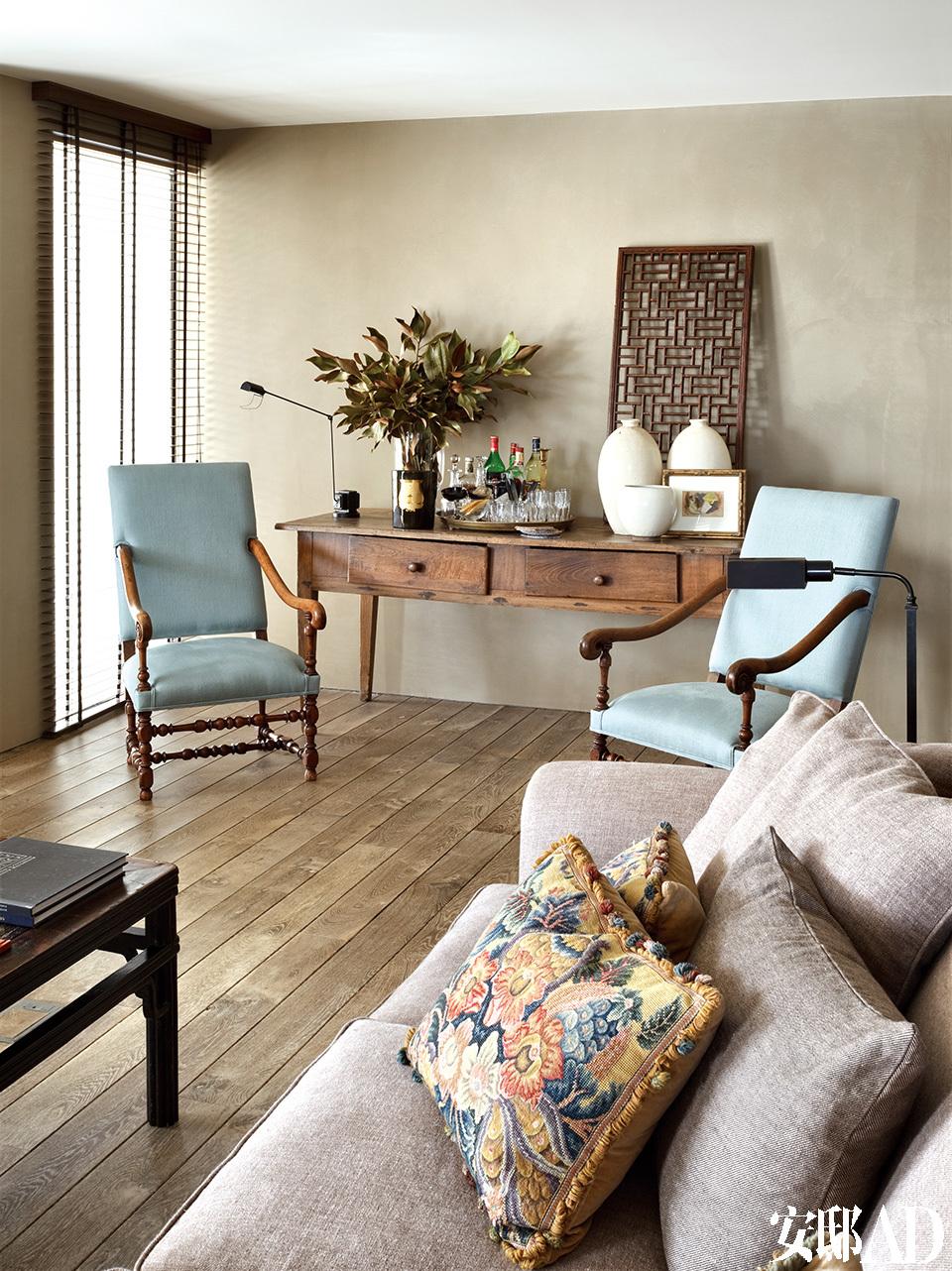 起居室一角放了两张法式扶手椅,旁边是19世纪西班牙方桌,上方以中式轩窗为装饰。