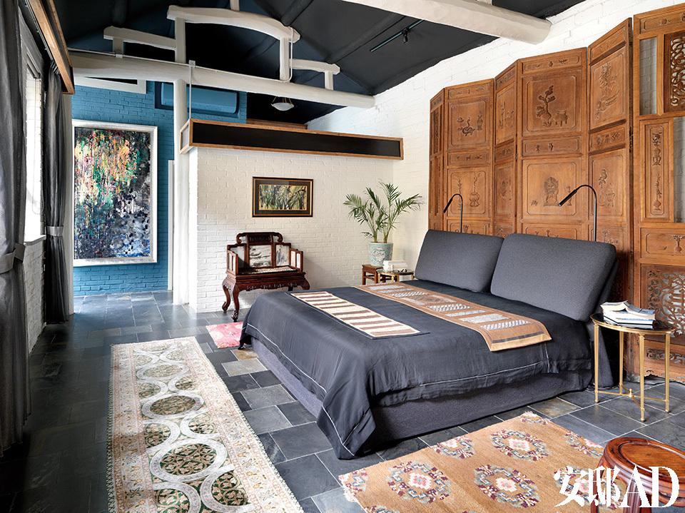 床上的织物是女主人设计的,后面蓝色墙壁上挂的画,则是小女儿Emily的作品,一家人简直人人都是艺术家。主卧室,床后有6块18世纪的中式屏风。床上搭的毯子是太太唐亮设计的,她喜欢收藏古董布料,再与现代布料手工拼接在一起。墙边有一把18世纪的老椅子。远处的一幅画是这个家的小女儿Emily的作品,吊顶的结构是原本就有的,萨洋将木梁刷成了白色,木梁下的黑色格罩是萨洋新添加的,里面装了LED灯。