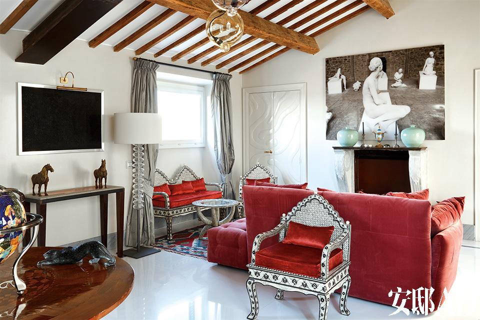 起居室一角,红色沙发与坐垫带来一丝活力与艺术气息。