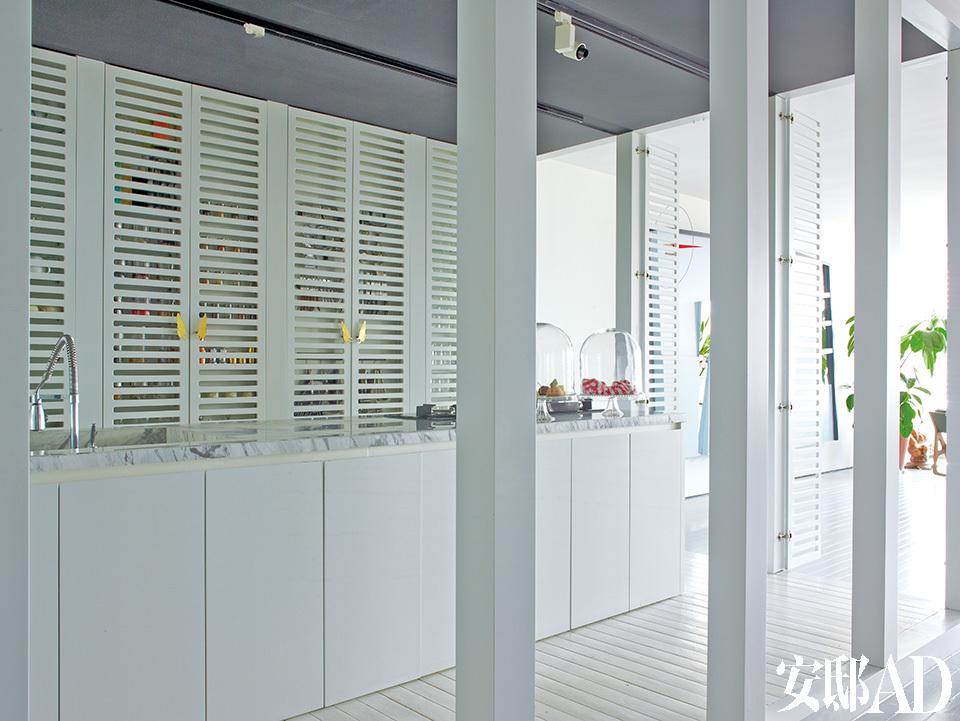 厨房是整间公寓的亮点,格纹木门既能分隔空间,又不至于让厨房和客厅看起来太割裂。