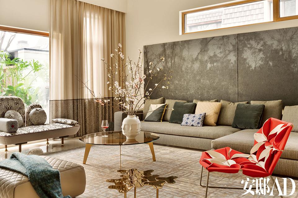 客厅中,窗边的My Beautiful Backside沙发由Nipa Doshi和Jonathan Levien设计,红色的Antibodi单椅由Patricia Urquiola设计,两件坐具皆来 自Moroso。左侧沙发上的蓝绿 色毯子来自Bo Concept北欧风 情,鲜花及Jonathan Adler花瓶 由野兽派特别提供。