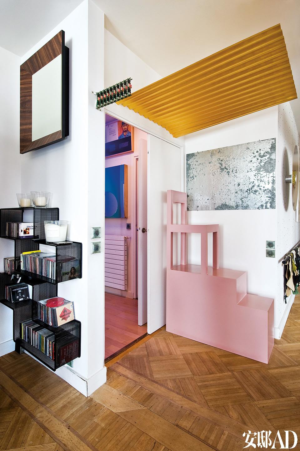 Mathieu Mategot设计的搁架储放着主人的CD,上方悬挂的墙饰来自Richard Artschwager,阶梯形状的粉色椅子由Alessandro Mendini设计,门上的波状金箔来自设计师Ann VeronicaJanssens,墙上银色的艺术品是一幅Franck David创作的拼图。