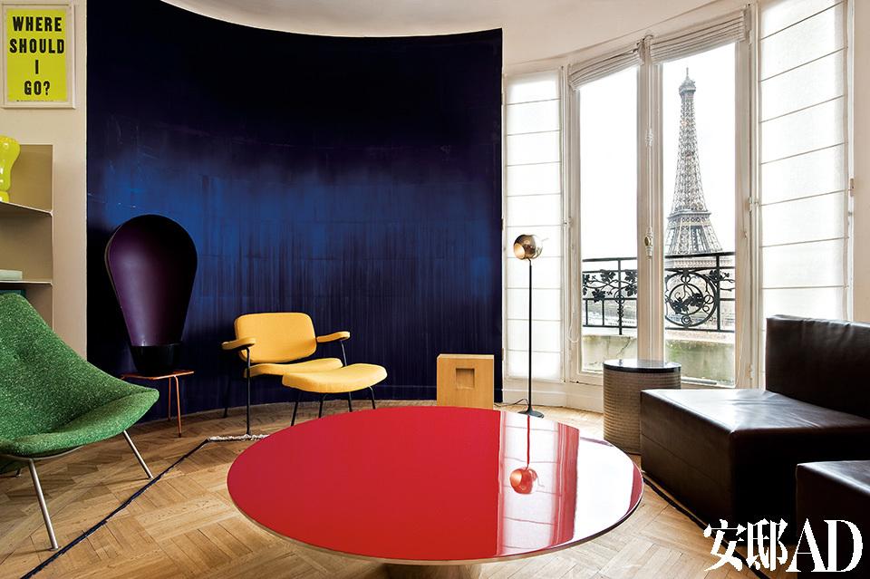 """客厅中,纹理斑驳的绿色椅子来自设计师Pierre Paulin,黄色扶手椅和脚凳也是他的作品。小凳子""""Object Missing""""的设计者是Konstantin Grcic,窗边的金属阅读灯来自设计师Gino Sarfatti,渐变蓝色墙面由Latifa Echakhch设计和制作,红色漆面的MGD咖啡桌是设计师Martin Szekely的作品。"""