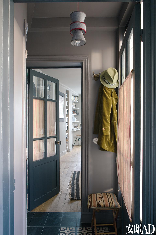 门厅中,吊灯由Marianne设计,材料为巴黎的Calligrane品牌纸,复古渔夫凳上的放着基里姆靠枕,水泥地砖来自Carocim,墙漆来自 Ressource。