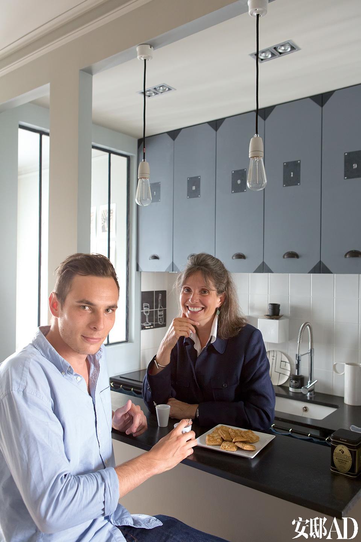 主人Robin和设计师母亲Marianne Evennou在厨房操作台旁。台面石料为来自津巴布韦的黑色花岗岩,橱柜由喷漆中密度纤维板打造。