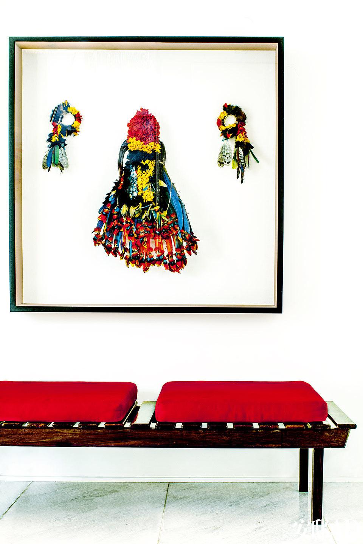 店淘来的长椅上方挂着亚马孙地区原始部落的羽毛头饰艺术品。