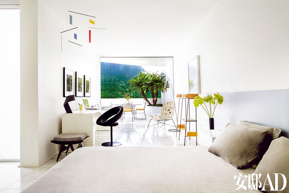 """""""任凭脑海中乌托邦式的巴西在这里肆意徜徉,毕竟这里就是我用来做梦和找回内心的地方。"""" 主卧完全和阳台融为一体。卧室内摆放着一张小型写字台。Ribbon台灯来自Habitat,圆椅出自Ricardo Fasabello之手。床头由涂漆木头制成,屋顶的装饰品购自巴西另一城市库里提巴。"""