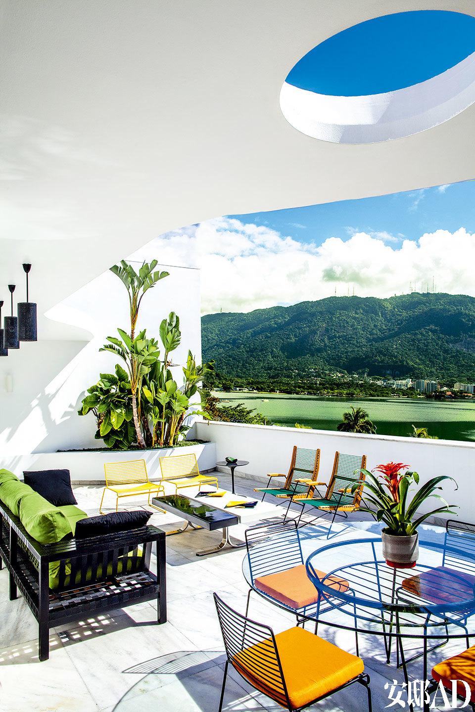 阳台上摆放着两把PVC吉他弦制成的上世纪50年代巴西风格的扶手椅,黄色单椅Hee来自品牌Hay。阳台保留了原本楼房的墙体和花园,凸显出上世纪60 年代的原生态特色。Dubai沙发来自Franccino Giardin。阳台上还摆放着Tulip桌子以及巴西风格的扶手椅。