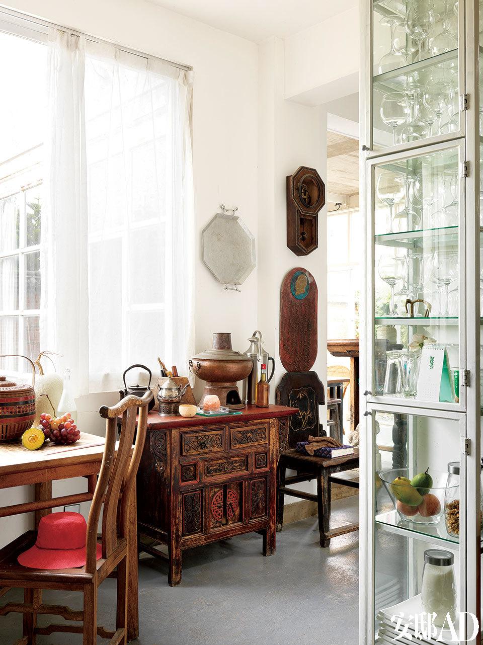 红色小桌子是淘来的本地旧家具,很漂亮,桌上是一个本地铜火锅,一把从日本到台湾地区再到美国再到大理的铸铁壶,一把德国老银壶。墙上一个能走却不准的旧钟,一块收来的文革铸铝语录板,一个美国旧物手工锻造的铝制茶盘。