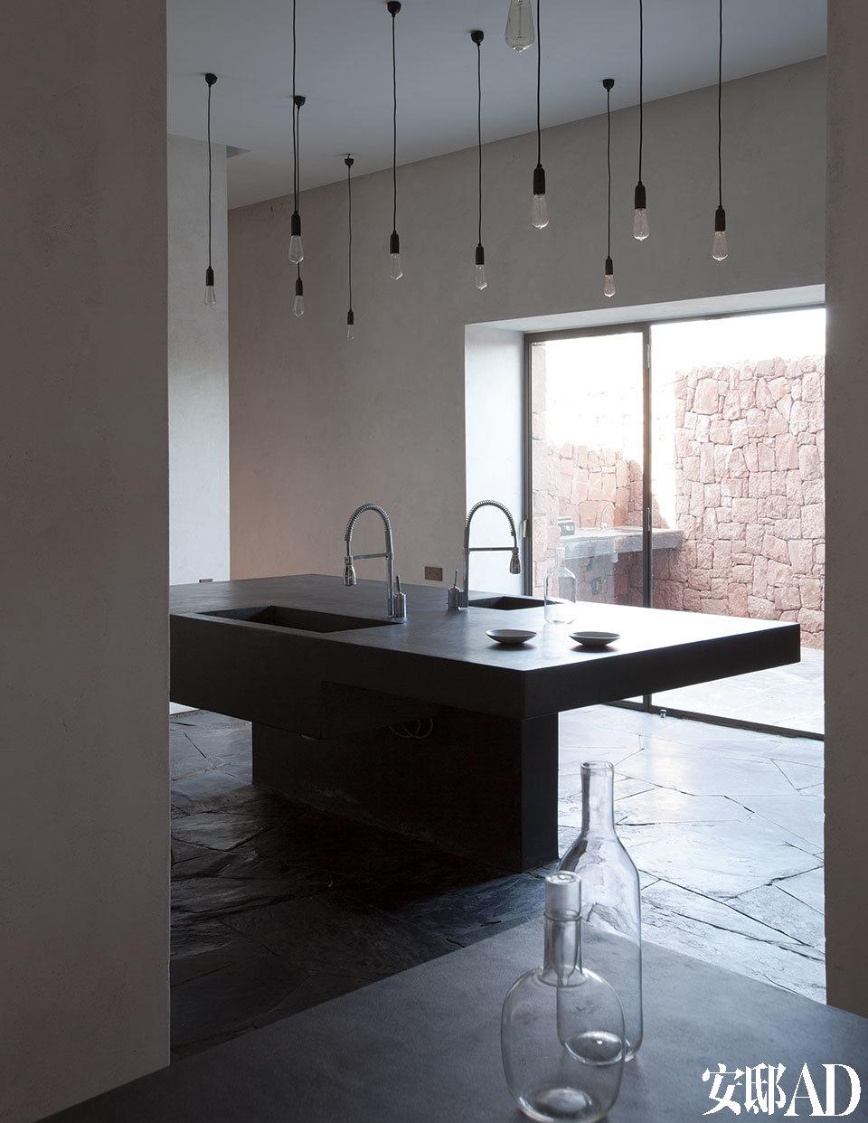 厨房中央的巨大岛台由水泥制成,也是Ko的设计,天花板上简单地吊着一些来自Zangra的灯泡,让气氛显得更加活跃。水龙头来自 Franke,瓷器由Nelson Sepulveda创作。
