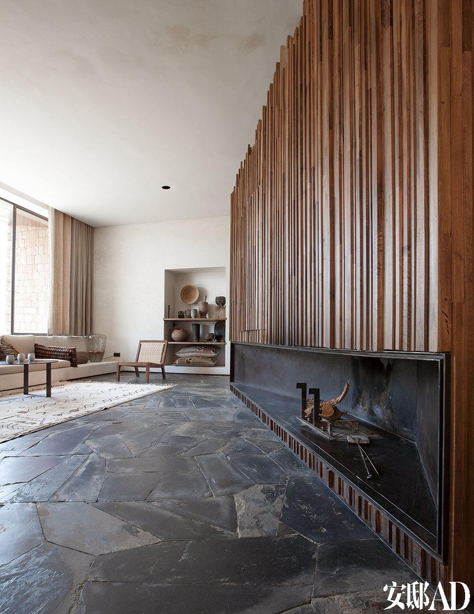 客厅中,壁炉周边镶嵌着满满的木条格栅,巧妙隐藏了电视机和一间木柴储存室。一间客厅中,长长的壁炉周围装饰着参差的木格栅,把电视机和木柴储藏室都隐藏了起来。胡桃木休闲椅由Ko设计,灵感来源于著名设计师Charlotte Perriand的作品,表面应用了当地植物埃及姜果棕(Doum)晒干后的编织面料。后面的壁龛里摆放着一系列北非柏柏尔风格的陶器和木制坛子,他们是 Karl Fournier从马拉喀什的跳蚤市场中淘来的。