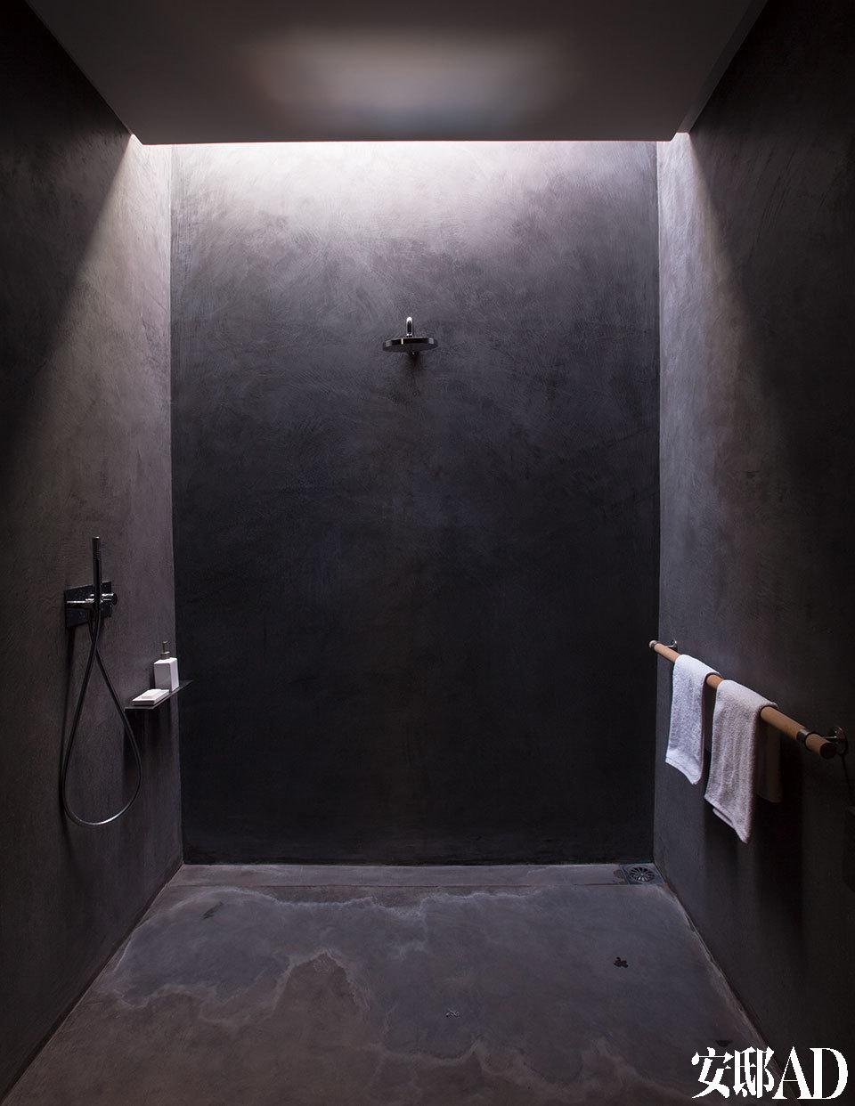 这间浴室由混凝土打造,在从顶部透来自然光下散发出神秘气息,龙头来自Fantini品牌。