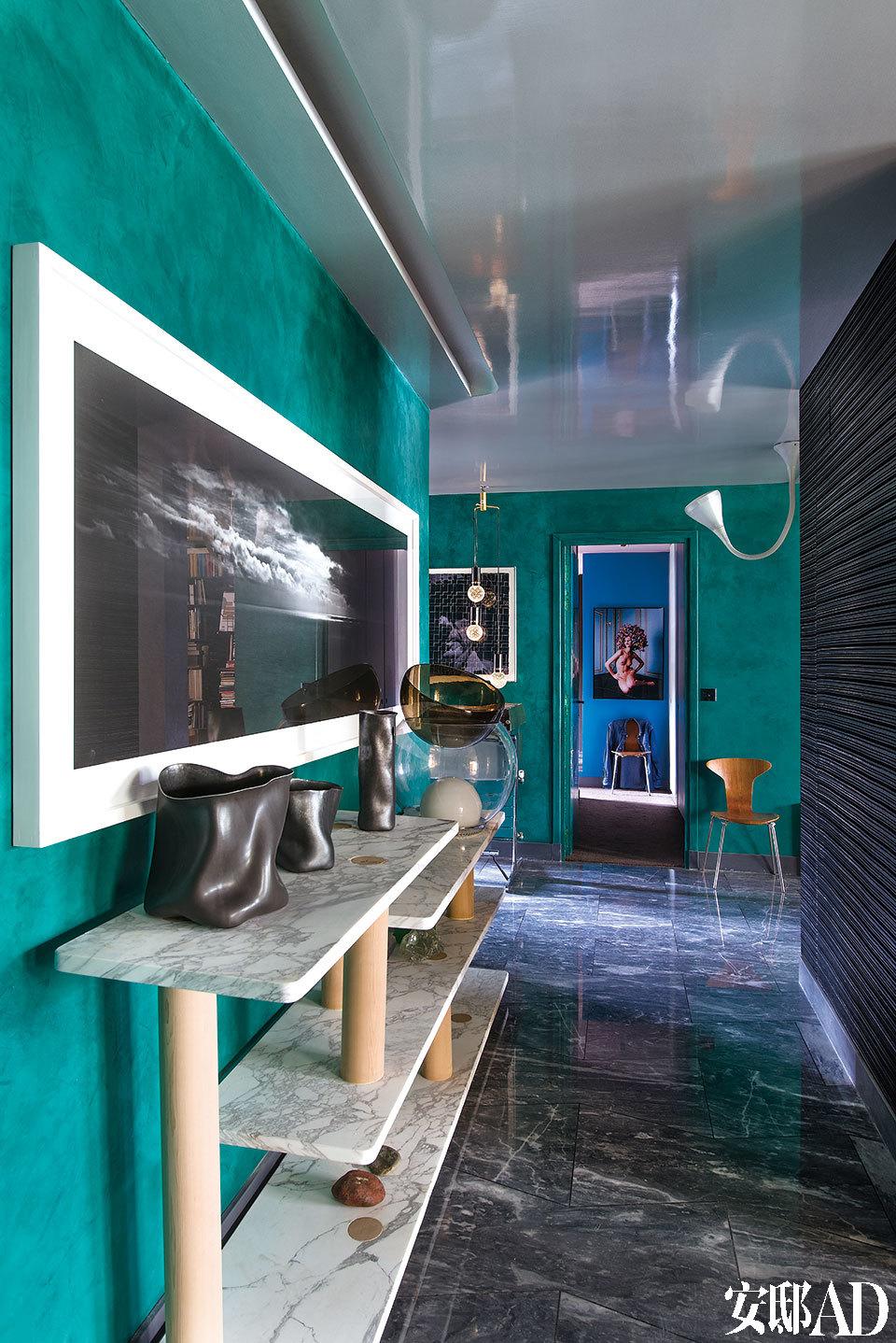 """门厅墙面采用维罗纳绿色织纹树脂,来自Signature Murale;摄影作品""""Electric Cinema IX""""(电动电影院9),作者Tom Fecht。长案是法布里斯的原创设计,大理石桌面,杉木桌腿。三个黑色玻璃瓷花瓶由Hyeyong Kim设计,来自巴黎的Galerie Downtown画廊;天花板灯""""Pipe"""",管子用弹性不锈钢制成,由Herzog & De Meuron设计。"""