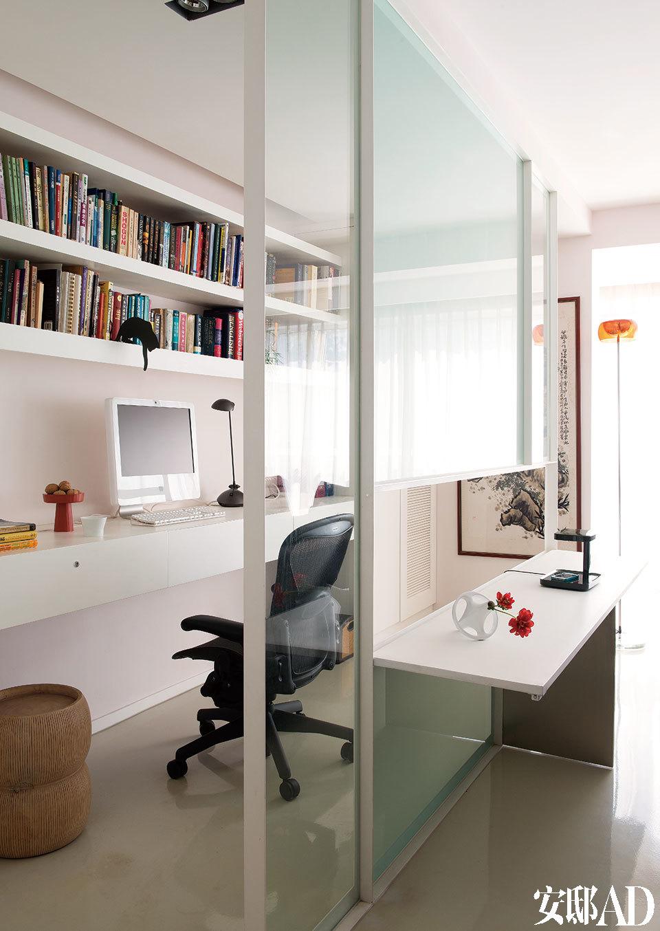 "Frank设计的钢架玻璃隔断中央,金属板可以放平成为一张临时的桌面。桌面上的白色花瓶为Bosa,黑色台灯为Flos品牌,均来自北京""家天地""。书 房中的座椅为Herman Miller品牌,小凳来自香港的OVO Home,书架上黑色的猫咪书挡同样是主人在新加坡旅行时的战利品。"